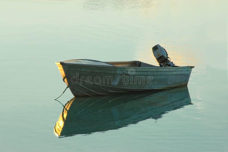 Schlauchboot befestigt auf einem glasigen Meer am Sonnenaufgang stockbild