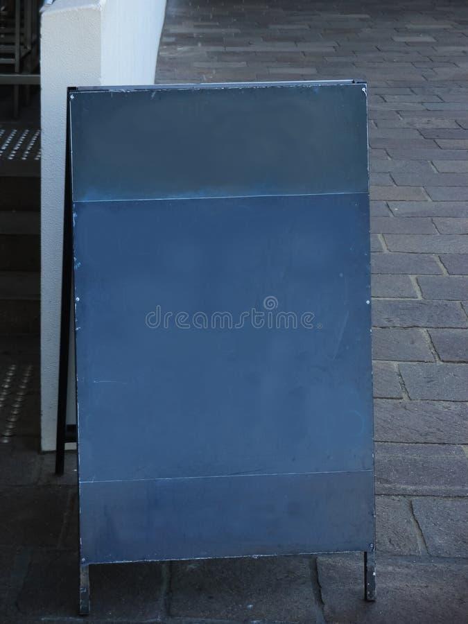 Schlecht gelöschtes leeres Tafelzeichen auf städtischem Bürgersteig neben Treppe - Raum für Text lizenzfreie stockfotografie