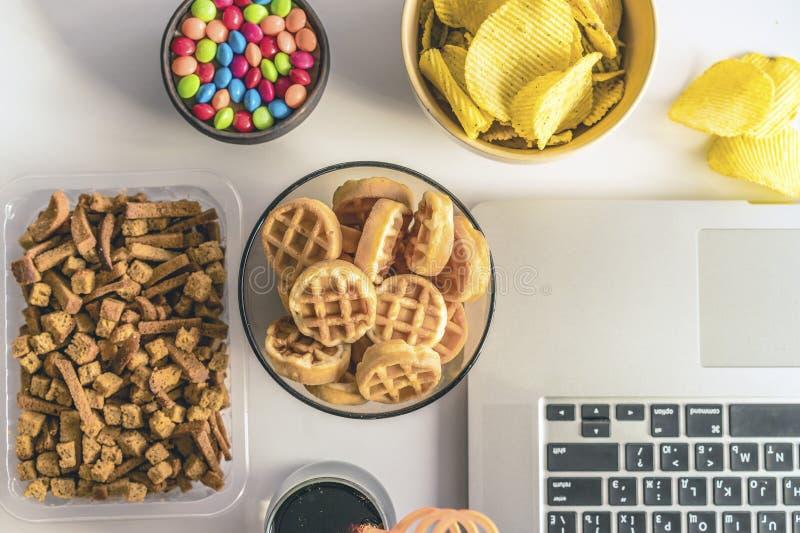 Schlechte Gewohnheit Arbeitsplatz mit Laptop, S??igkeiten, Chips, Kolabaum auf wei?em Hintergrund stockfoto