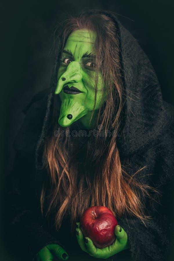 Schlechte Hexe, die einen faulen Apfel hält lizenzfreie stockfotos