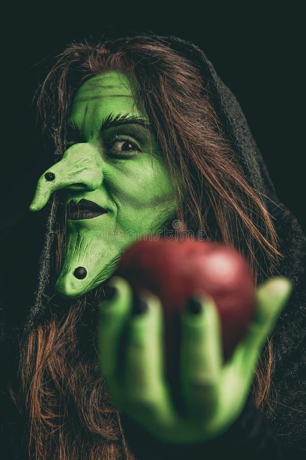 Schlechte Hexe, die einen roten Apfel hält stockfotografie