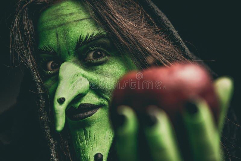 Schlechte Hexe, welche die Kamera hält einen roten Apfel betrachtet stockbilder
