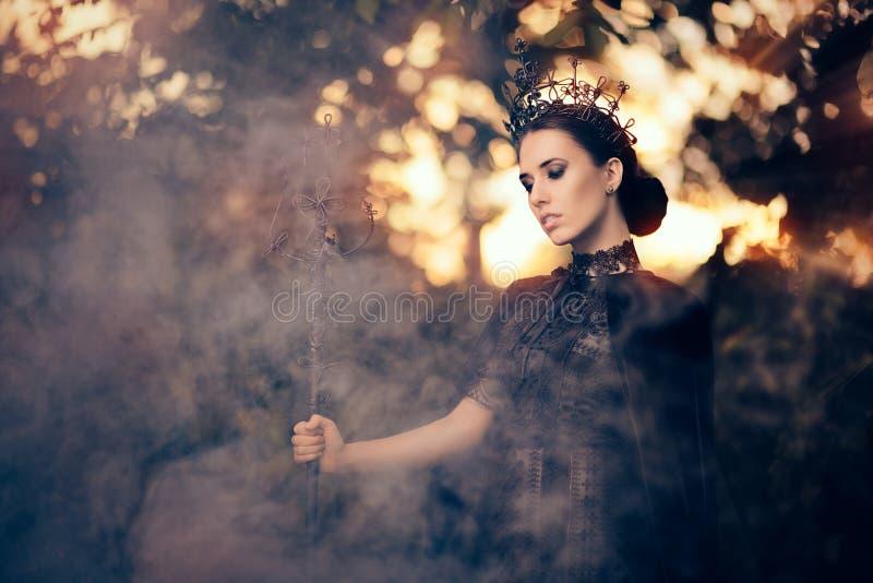 Schlechte Königin, die Zepter in Misty Forest hält stockfoto