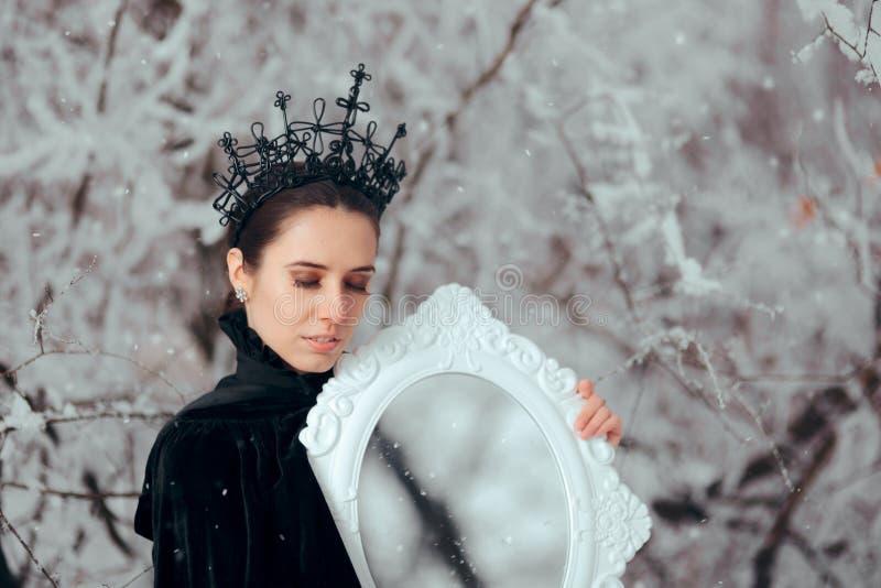 Schlechte Königin mit magischem Spiegel im Winter-Märchenland lizenzfreies stockfoto