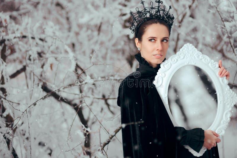 Schlechte Königin mit magischem Spiegel im Winter-Märchenland lizenzfreie stockbilder