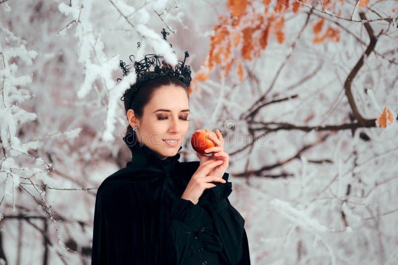 Schlechte Königin mit vergiftetem Apple im Winter-Märchenland lizenzfreie stockbilder