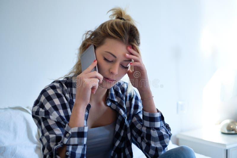 Schlechte Nachrichten der traurigen Anhörung des Mädchens durch das Telefon lizenzfreies stockfoto