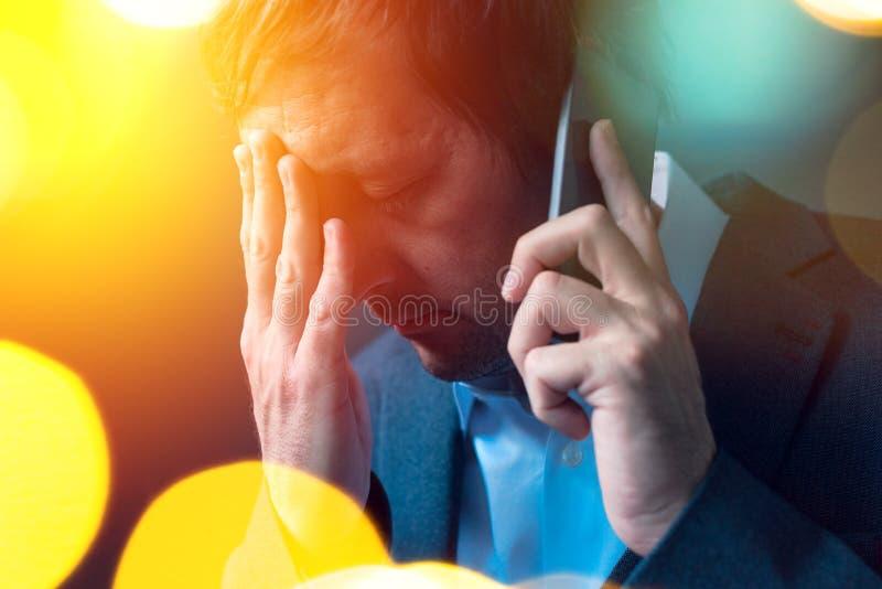Schlechte Nachrichten, Geschäftsmann, der unangenehmes Telefongespräch leitet lizenzfreies stockbild