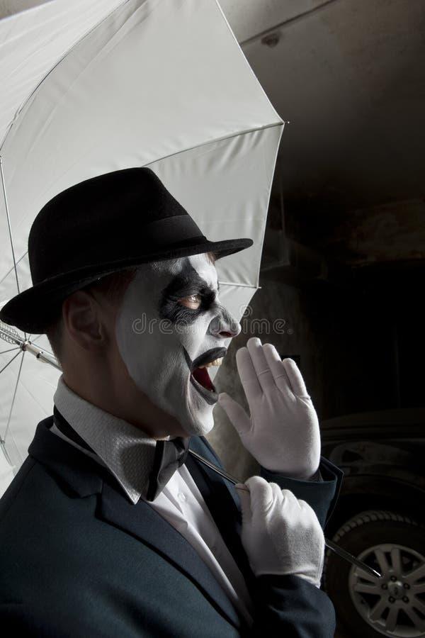 Schlechter Clown, der weißen Regenschirm hält lizenzfreie stockbilder