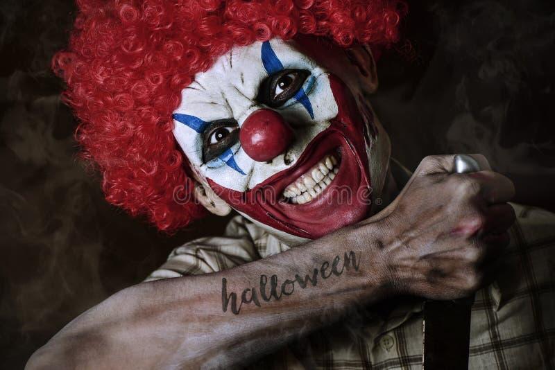 Schlechter Clown mit dem Wort Halloween in seinem Arm lizenzfreie stockfotos