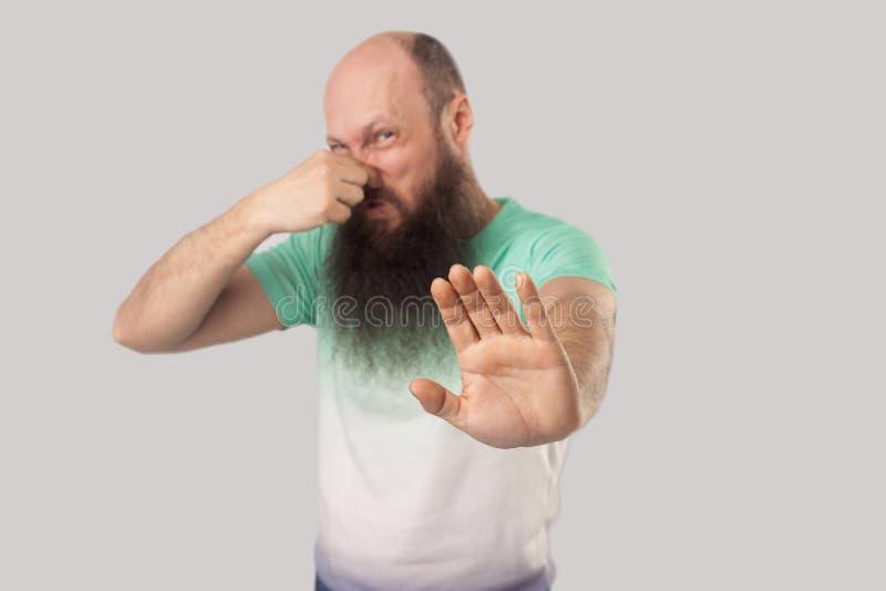 Schlechter Geruch, stoppen Porträt der verwirrten Mitte alterte kahlen Mann mit langem Bart in hellgrüner T-Shirt Stellung und bl stockfotografie
