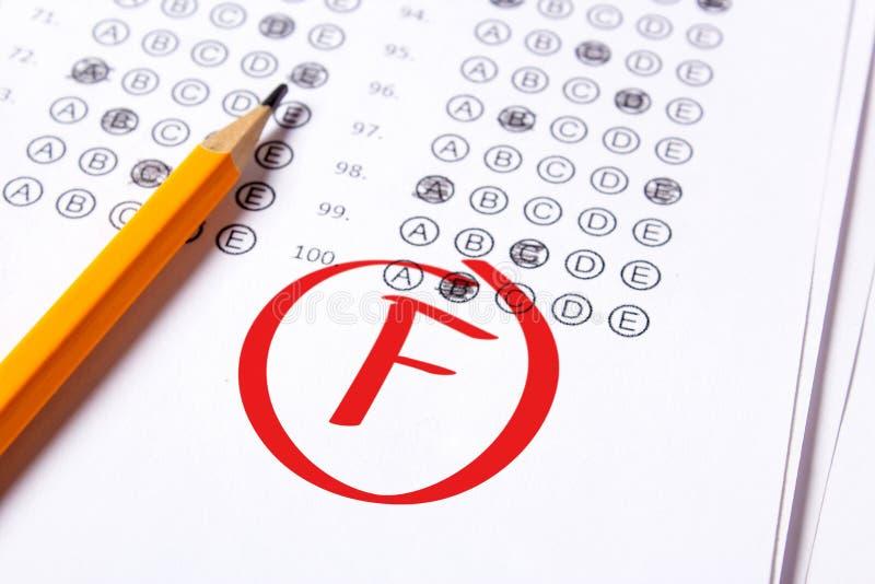 Schlechter Grad F wird mit rotem Stift auf die Tests geschrieben lizenzfreies stockbild