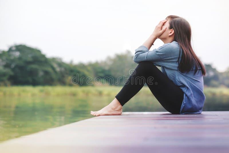 Schlechtes Tageskonzept Traurigkeits-Frau, die durch den Fluss sitzt stockfotografie