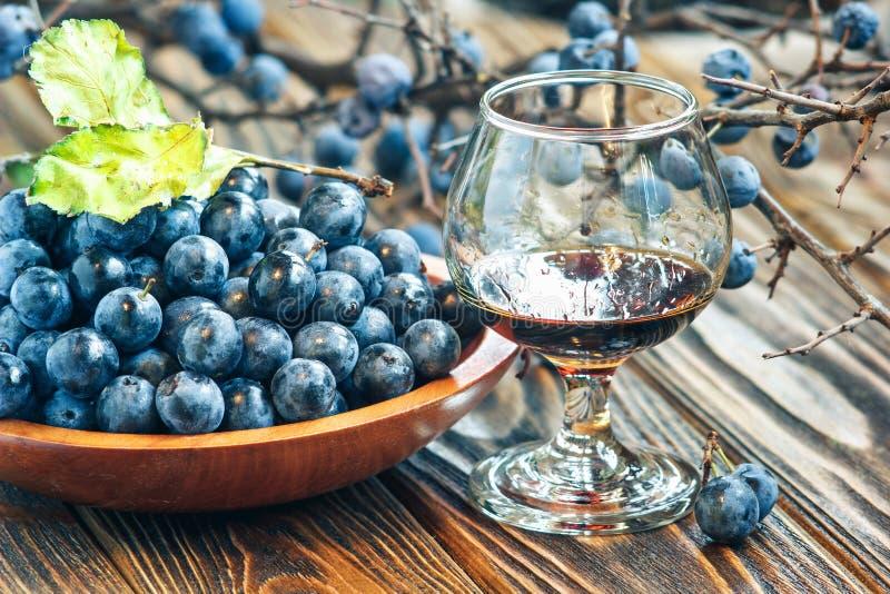 Schlehen-Gin Glas selbst gemachte helle süße rötlich braune Flüssigkeit des Schlehdorns Schlehe-aromatisierter Likör oder Wein stockbilder