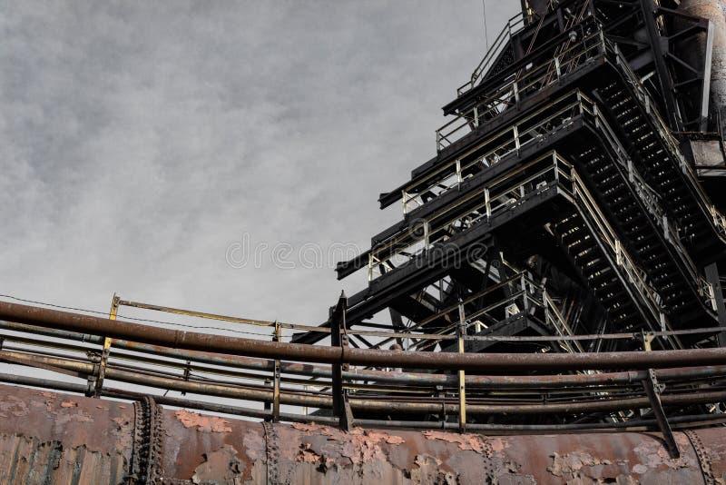 Schleifen von industriellen Rohren und von Treppe, aufgegebenes Stahlwerk lizenzfreie stockfotografie