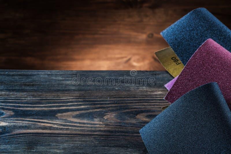 Schleifpapierblätter auf dunklem Holz der Weinlese lizenzfreie stockbilder
