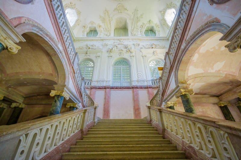 Schleissheim Tyskland - Juli 30, 2015: Forntida trappuppgång inom slottbyggnad från ner att se upp, härliga kungliga garneringar arkivbild