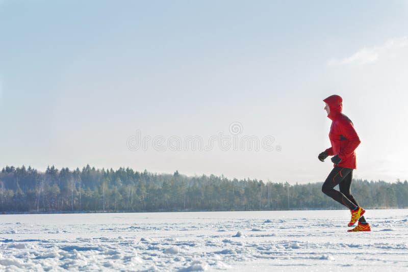 Schleppen Sie den laufenden Läufer, der draußen rote schützende Sportkleidung auf Winterschulungseinheit trägt stockbilder