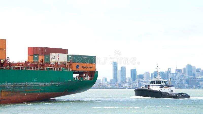 Schlepper AHBRA Frachtschiff SEASPAN HAMBURG FREI unterstützend, um zu manövrieren stockfotografie