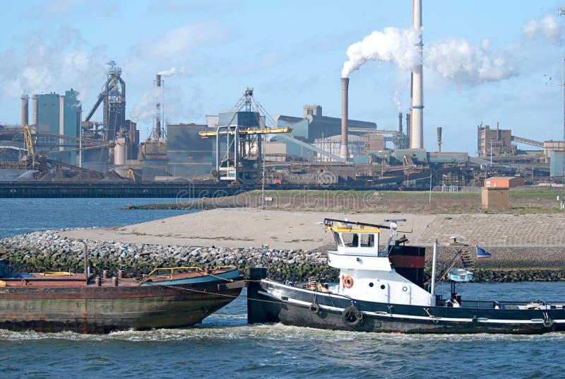 Schlepper, der Frachtschiff im Hafen drückt stockfotografie