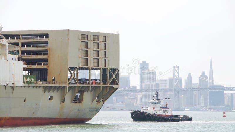 Schlepper FREIHEIT, die Frachtschiff MATSONIA unterstützt, um zu manövrieren stockbilder