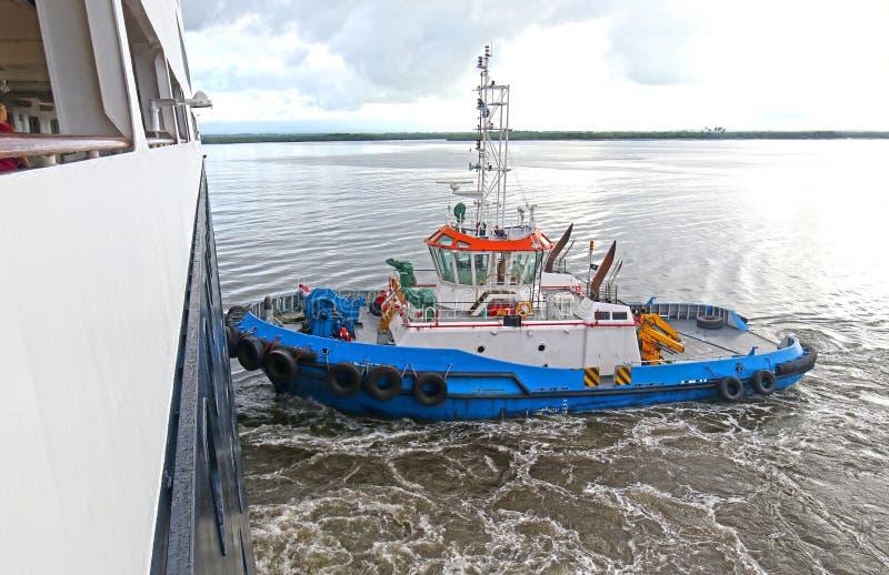Schlepperboot, das ein Kreuzschiff am Hafen von Corinto, Nicaragua drückt lizenzfreies stockbild