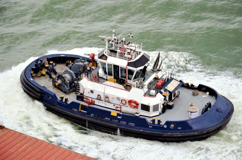 Schlepperboot, das zum Containerschiff unterst?tzt lizenzfreie stockbilder