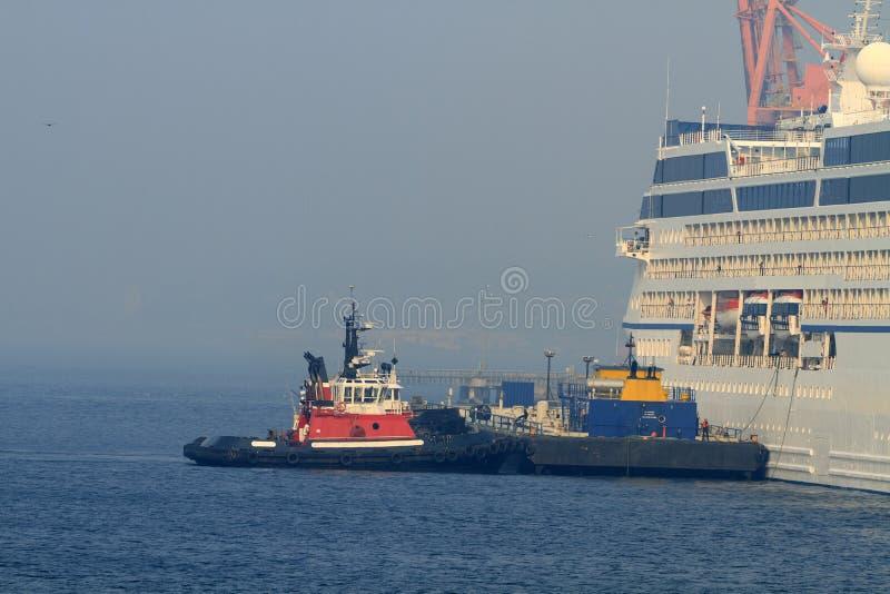 Schlepperboot und -lastkahn helfen einem Kreuzschiffdock stockfoto