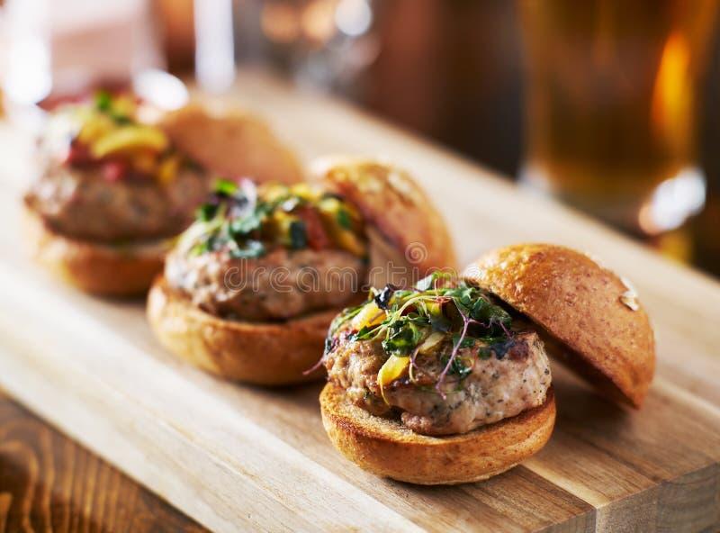Schleppseil von drei Minitruthahnburgerschiebern mit Briochebrötchen lizenzfreie stockfotos