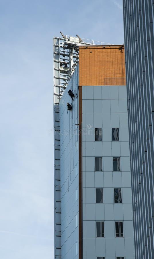 Schleppseilmann, der an den Seilen an einem Gebäude hängt stockfoto