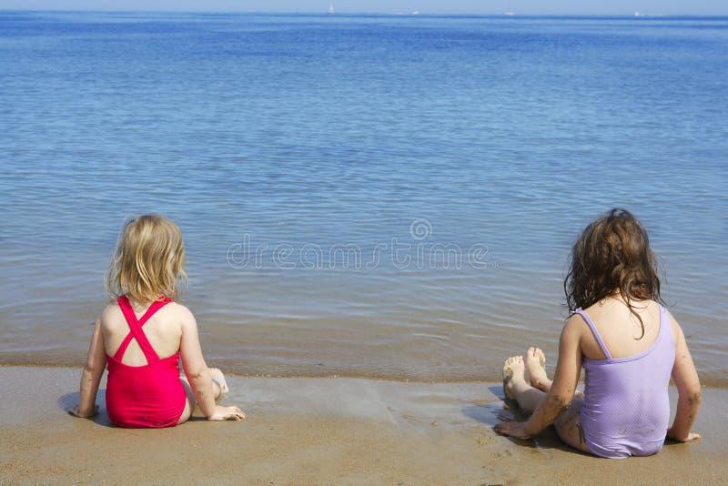 Schleppseilschwestern sitzen auf Badeanzugbadeanzug des Strandes stockbilder