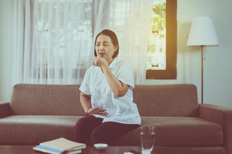 Schlick asiatische SeniFrau, die zu Hause eine Tablette oder Kapseln einnimmt stockbilder