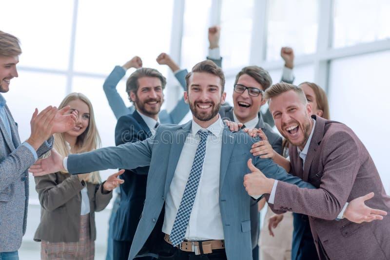 Schließen Glückliches Geschäftsteam umarmt ihren Führer lizenzfreies stockfoto