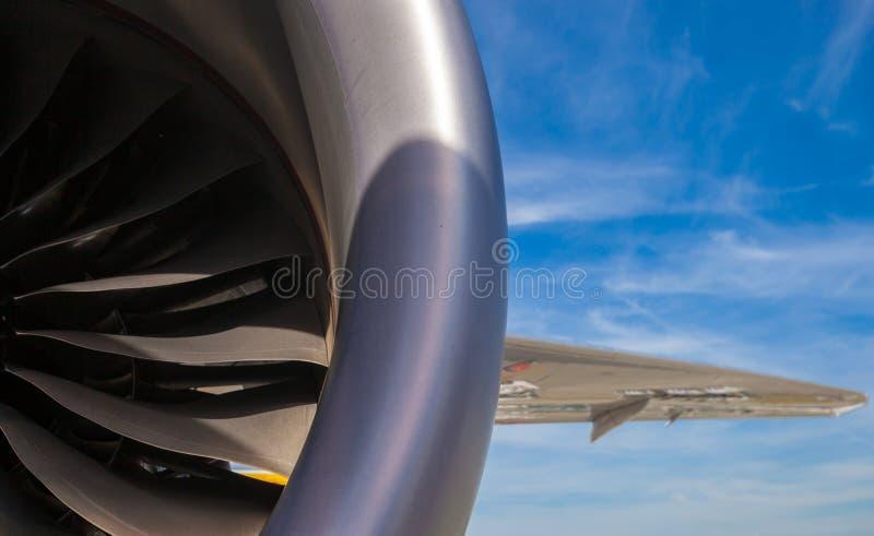 Schließen Sie herauf Abschnitt des Strahltriebwerks mit Titanblättern und Abschnitt des Flügels auf einem Hintergrund des blauen  lizenzfreie stockfotografie