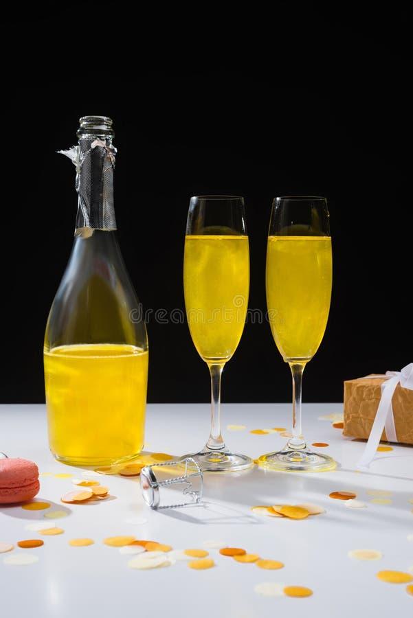 schließen Sie herauf Ansicht der Flasche und der Gläser des gelben Champagners, des macaron und des Geschenks auf Oberfläche lizenzfreies stockbild