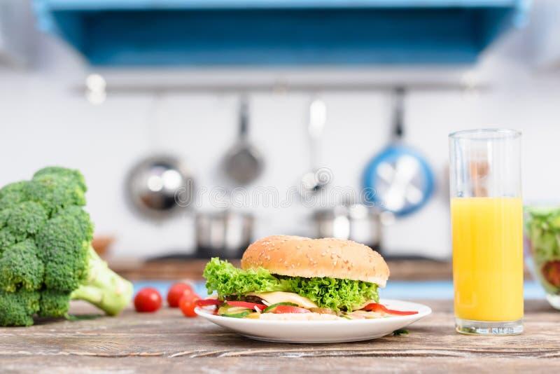 schließen Sie herauf Ansicht des Burgers auf Platte, frischem Brokkoli und Glas Saft auf hölzerner Tischplatte lizenzfreie stockbilder