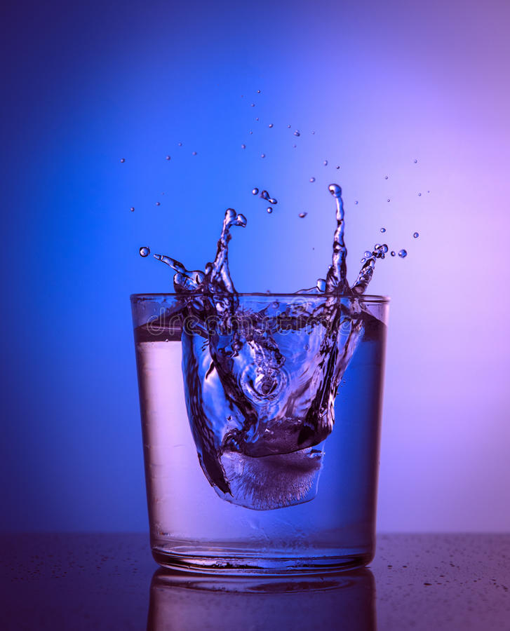 Schließen Sie herauf Ansicht des Eisspritzens im Wasser auf rosa und blauer Steigung lizenzfreie stockfotos