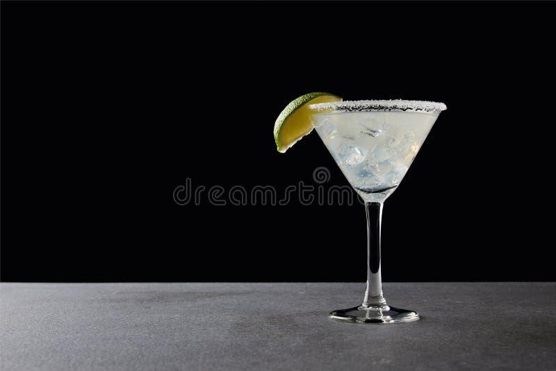 schließen Sie herauf Ansicht des geschmackvollen Margaritacocktails mit Kalk und Eis auf Tischplatte auf Schwarzem lizenzfreie stockbilder