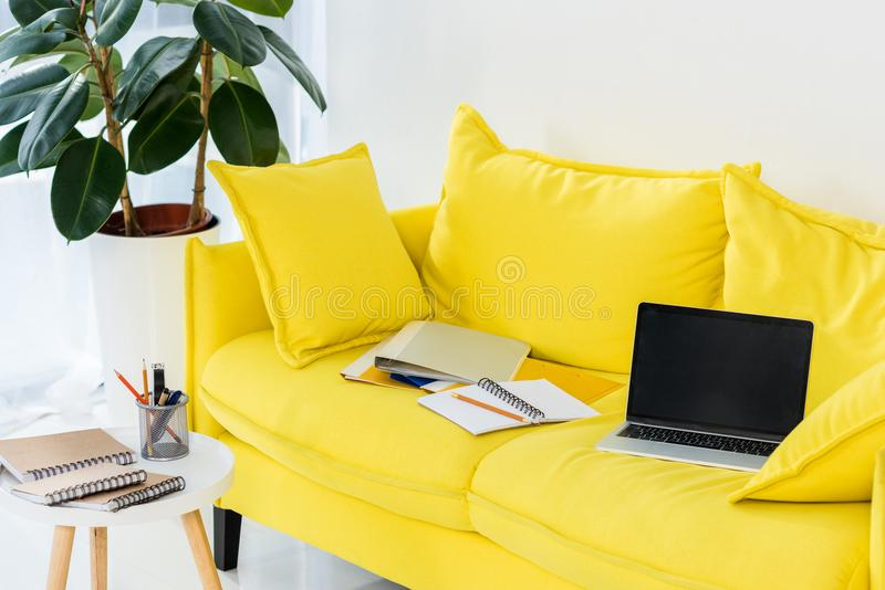 schließen Sie herauf Ansicht des Laptops, der Notizbücher und der Ordner auf gelbem Sofa lizenzfreies stockfoto