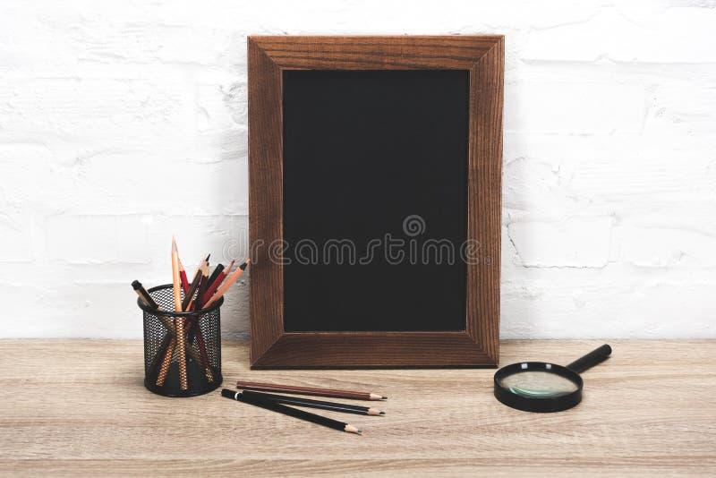 schließen Sie herauf Ansicht des leeren Fotorahmens, -lupe und -Büroartikels stockfotos