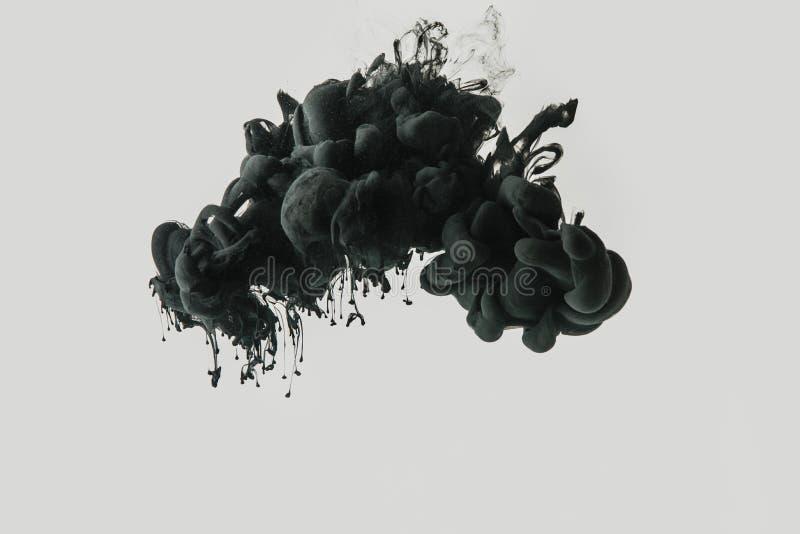 Schließen Sie herauf Ansicht des schwarzen Farbenspritzens im Wasser, das auf Grau lokalisiert wird stockfotos