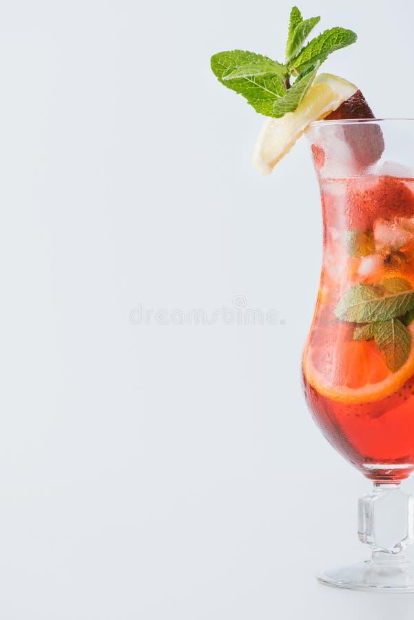schließen Sie herauf Ansicht des Sommererdbeercocktails mit Eis, Minze, Zitrone und orange Stücken stockfotos