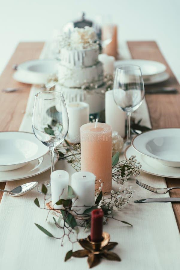 schließen Sie herauf Ansicht des stilvollen Gedecks mit Kerzen, leeren Weingläsern und Platten lizenzfreie stockfotografie