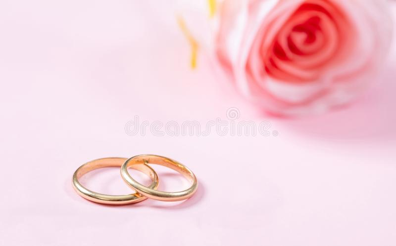 Schließen Sie herauf Ansicht von goldenen Eheringen und von undeutlichen Rosarose, Kopienraum, auf einem rosa Hintergrund stockfotografie