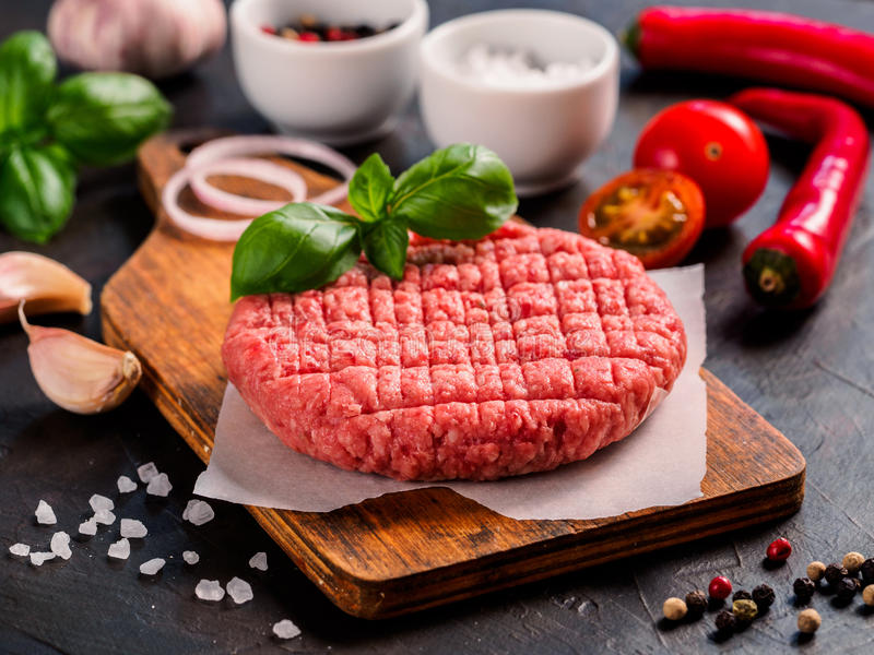 Schließen Sie herauf Ansicht von zwei Steakkoteletts des rohen Fleisches für Burger mit Gemüse stockfotos