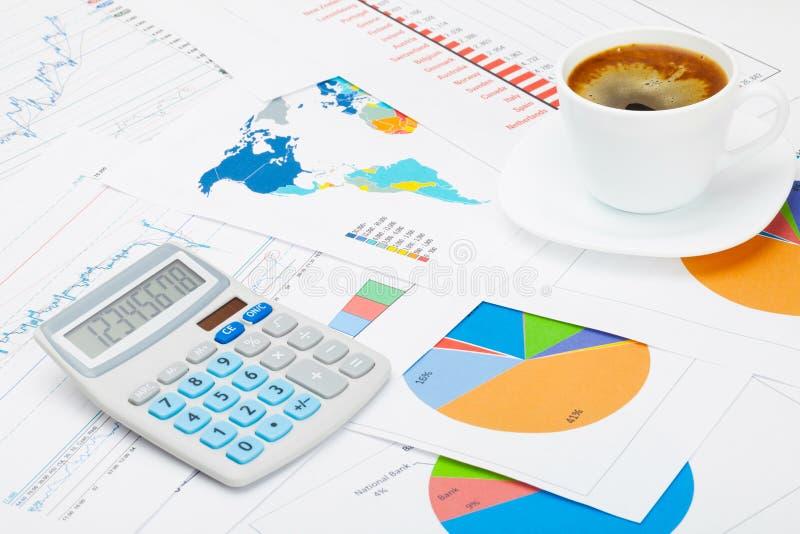Schließen Sie herauf Atelieraufnahme einer Kaffeetasse und des Taschenrechners über einigen Diagrammen stockbilder