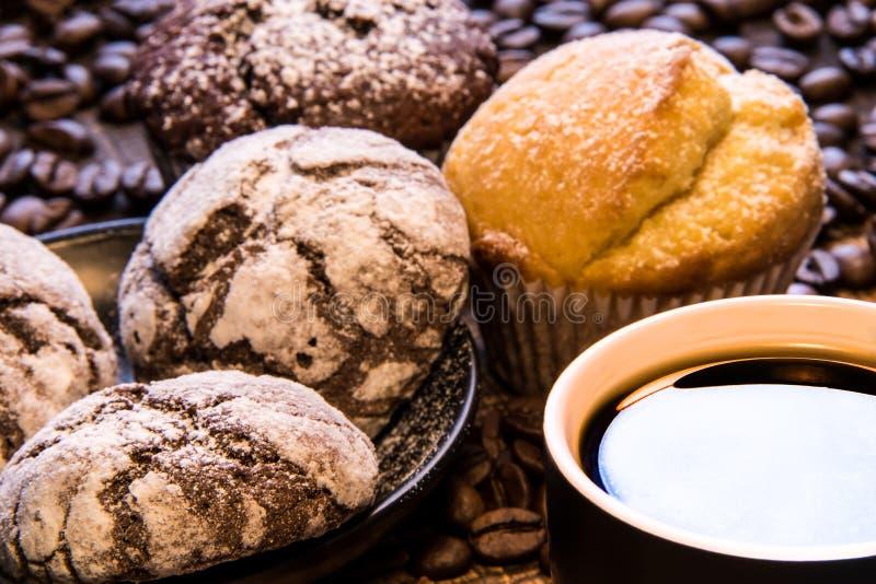 Schließen Sie herauf Becher schwarzen Kaffee nahe bei einer Platte von den Schokoladenplätzchen, die mit Puderzucker und auf der  lizenzfreie stockfotos