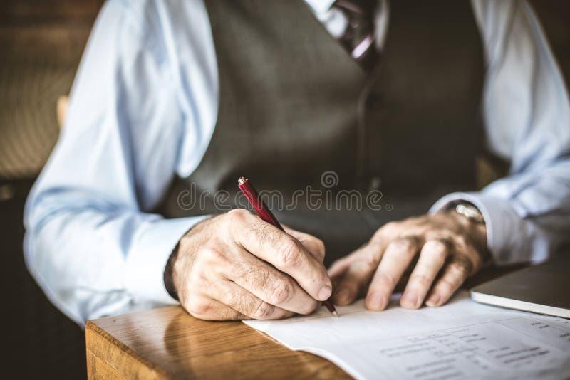 Schließen Sie herauf Bild des älteren Geschäftsmannes unterzeichnen herein Papiere stockfotos