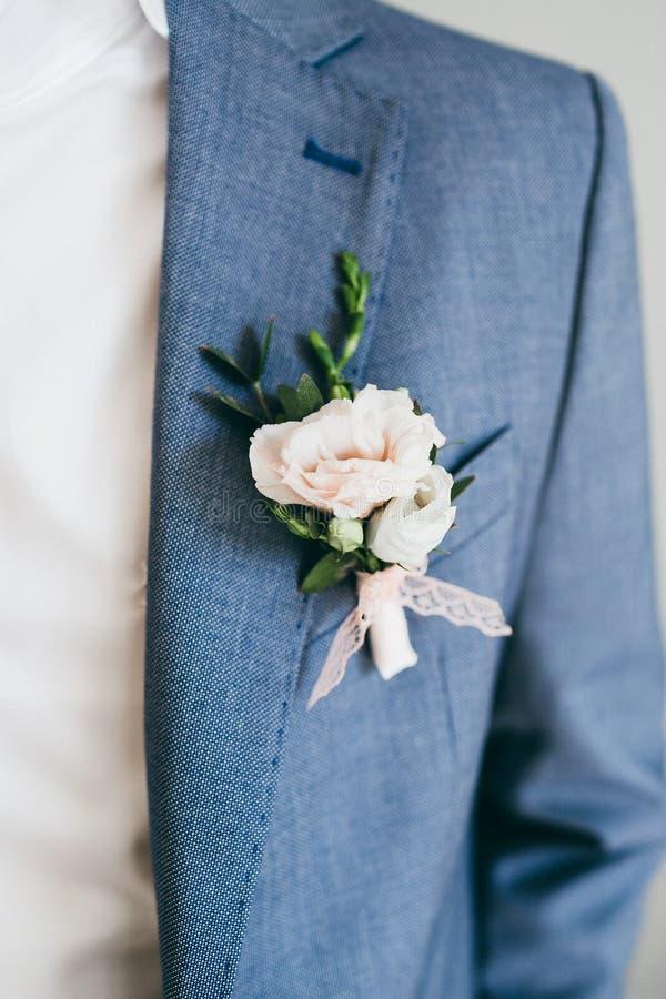 Schließen Sie herauf Bild des schönen Boutonniere auf der Bräutigam ` s Jacke Weichzeichnung auf Boutonniere gestaltungsarbeit lizenzfreies stockfoto