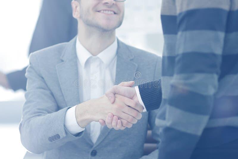 Schließen Sie herauf Bild des Teilhaberhändedrucks über Schreibtisch während der Sitzung lizenzfreies stockfoto